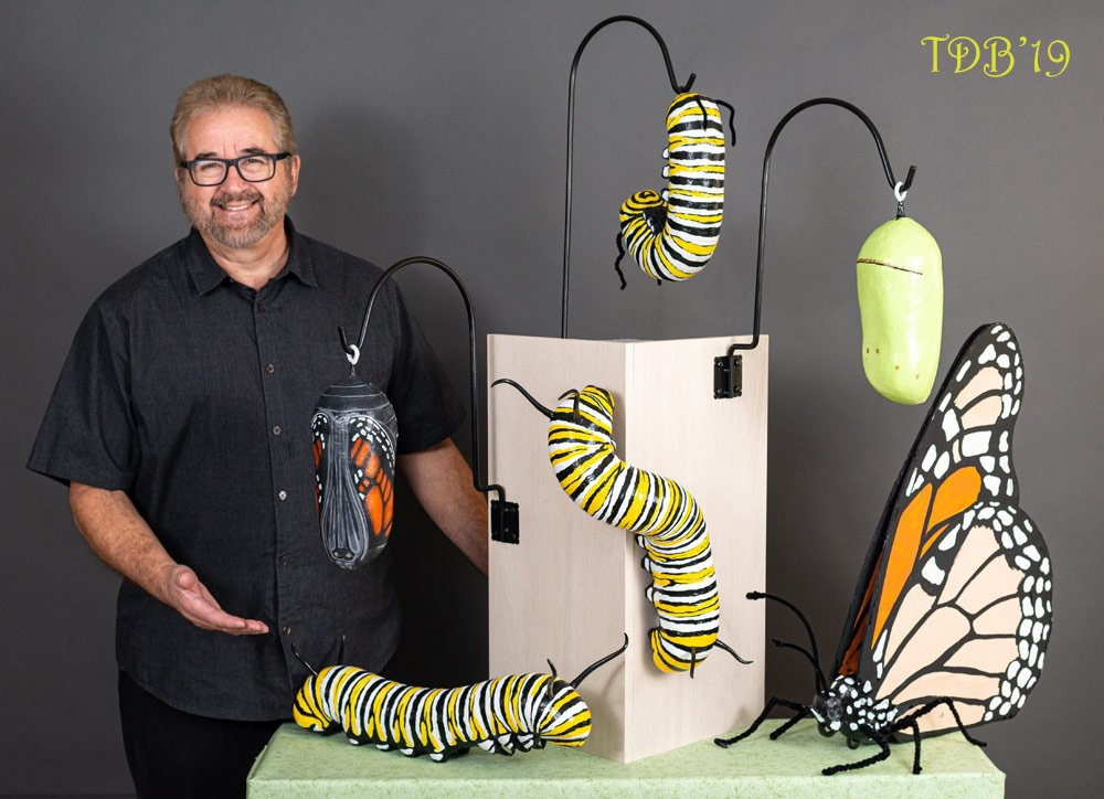 Artist Randy Peterson with his monarch life cycle art sculptures- butterfly gift ideas